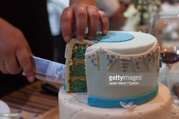 Cropped Hand Of Child Cutting Birthday Cake