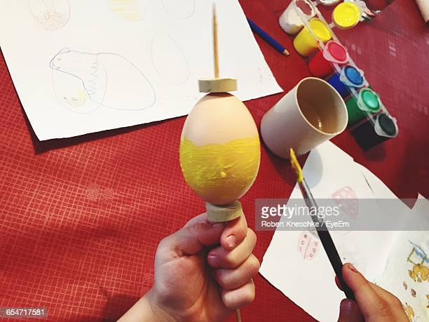 Cropped Hand Of Child Painting Egg Over Table