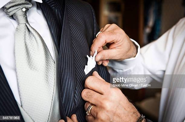 Cropped Hand Of Man Adjusting Handkerchief Of Friend