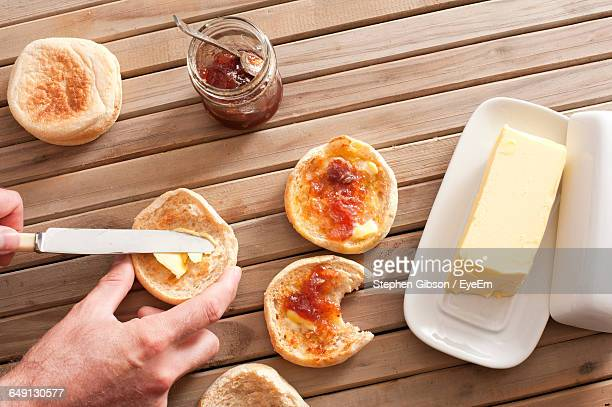 Cropped Hand Of Man Applying Butter And Jam On Bread Using Table Knife