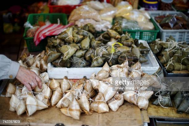Cropped Hand Of Man Buying Zongzi At Market Stall