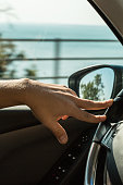 Cropped Hand Of Man Driving Car