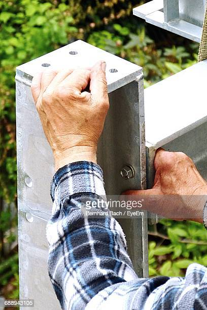 Cropped Hand Of Man Fixing Metal Structure