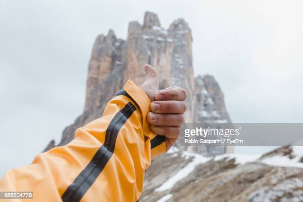 Cropped Hand Of Man Gesturing Thumbs Up Against Rock Formations