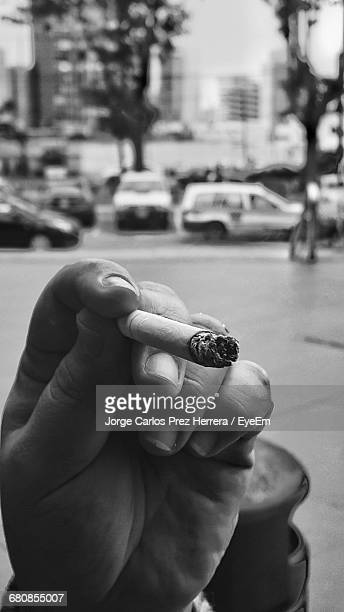 Cropped Hand Of Man Holding Burning Cigarette On Street
