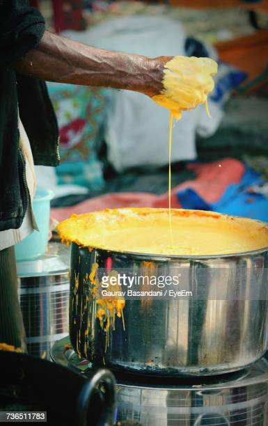 Cropped Hand Of Man Preparing Batter In Container