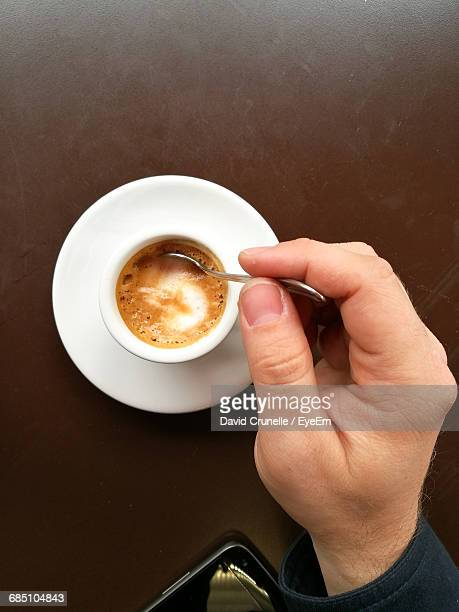 Cropped Hand Of Man Stirring Coffee With Spoon On Table