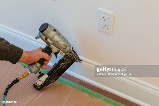 Cropped Hand Of Man Using Drill On Wall At Home