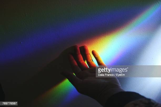 Cropped Hand Of Man With Prism By Wall