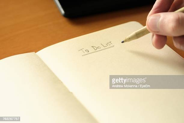 Cropped Hand Of Man Writing In Notepad At Desk In Office