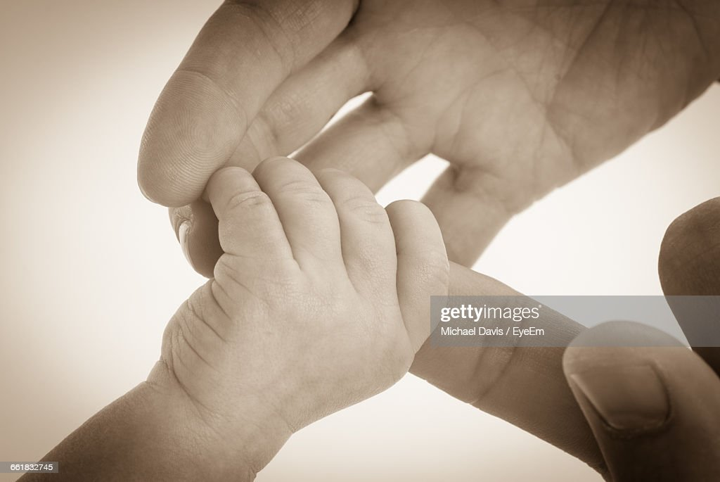 Cropped Hand Of Mother Holding Child Against White Background