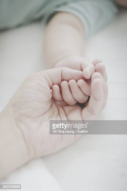 Cropped Hand Of Mother With Baby On Bed