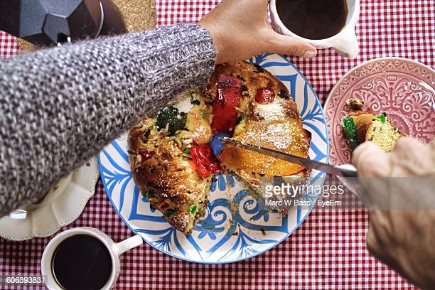 Cropped Hand Of Person Cutting Bolo Rei On Table During Christmas
