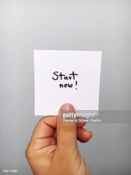 Cropped Hand Of Person Holding Adhesive Note With Start Now Text Against Gray Background