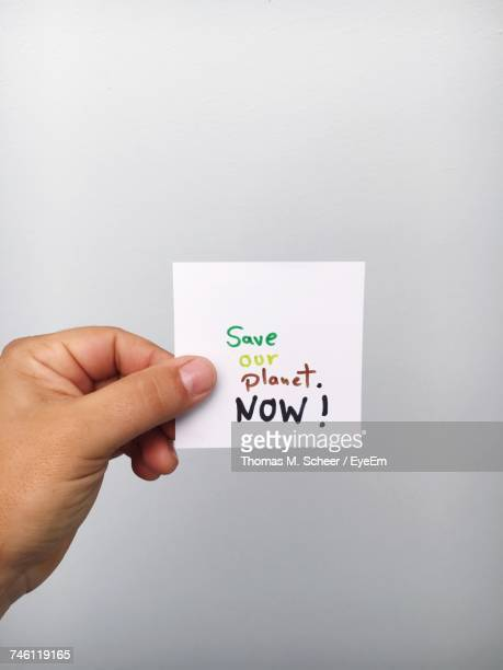 Cropped Hand Of Person Holding Adhesive Note With Text Against Gray Background