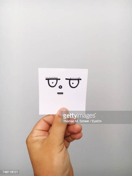 Cropped Hand Of Person Holding Angry Emoticon Face On Paper Against Gray Background