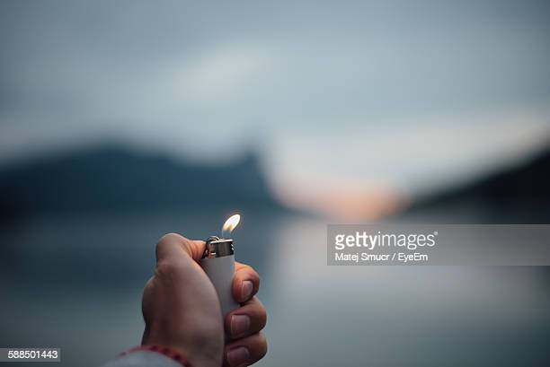 Cropped Hand Of Person Holding Cigarette Lighter