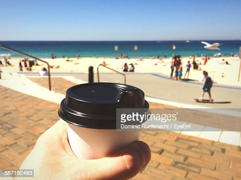 Cropped Hand Of Person Holding Disposable Cup At Beach