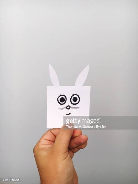 Cropped Hand Of Person Holding Easter Bunny Drawn On Adhesive Note Against Gray Background