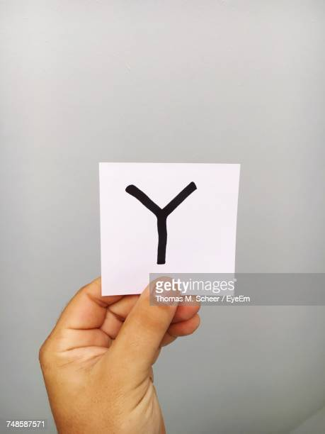 Cropped Hand Of Person Holding Letter Y On Adhesive Note Against Gray Background