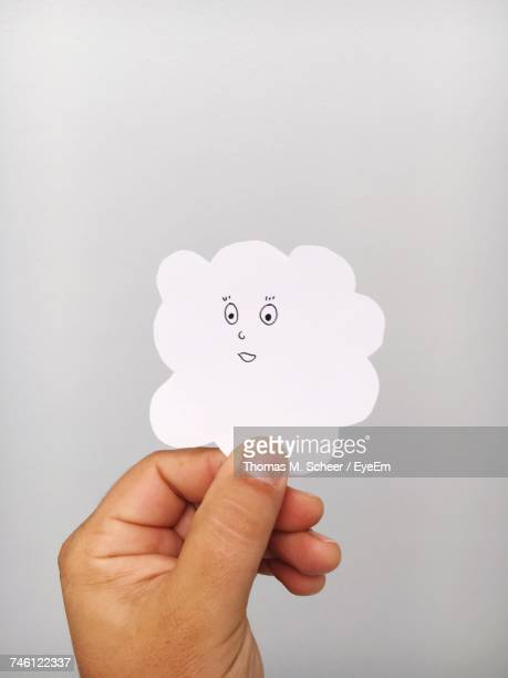 Cropped Hand Of Person Holding Paper Cloud Against Gray Background