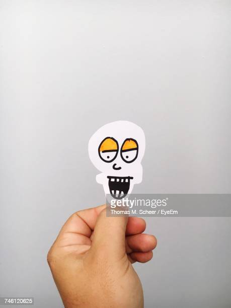 Cropped Hand Of Person Holding Paper Skull Against Gray Background