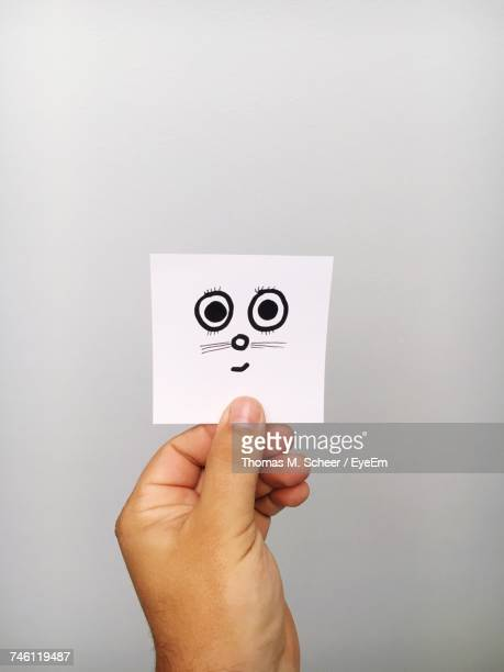 Cropped Hand Of Person Holding Rabbit Drawn On Adhesive Note Against Gray Background