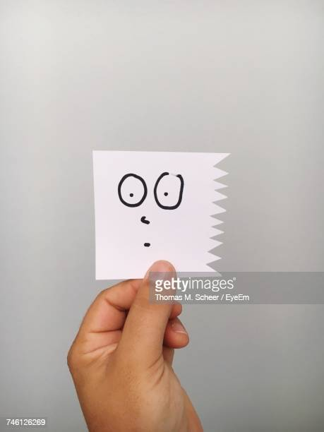 Cropped Hand Of Person Holding Shocked Emotion Face On Paper Against Gray Background