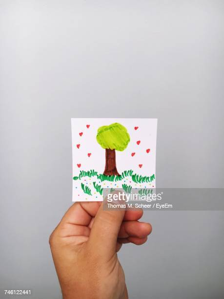 Cropped Hand Of Person Holding Tree Drawn On Adhesive Note Against Gray Background