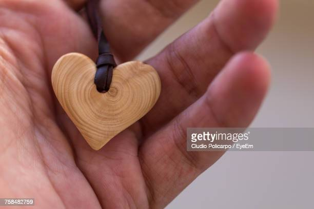 Cropped Hand Of Person Holding Wooden Heart Shape Locket