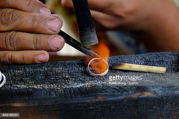 Cropped Hand Of Person Making Ring On Wood