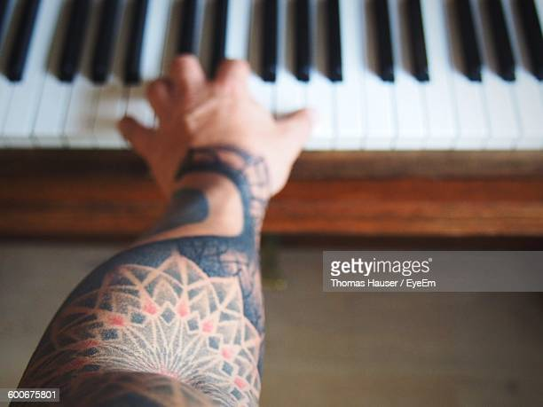 Cropped Hand Of Person With Tattoo Playing Piano