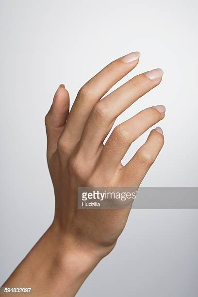 Cropped hand of woman against white background