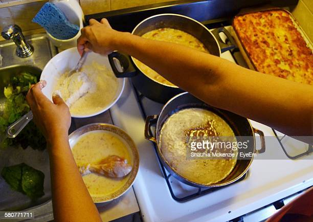 Cropped Hand Of Woman Cooking Food In Kitchen