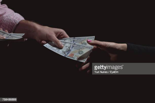 Cropped Hand Of Woman Giving Paper Currency To Friend Against Black Background