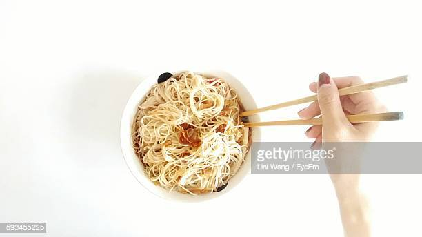 Cropped Hand Of Woman Holding Chopsticks By Rice Noodles Against Table