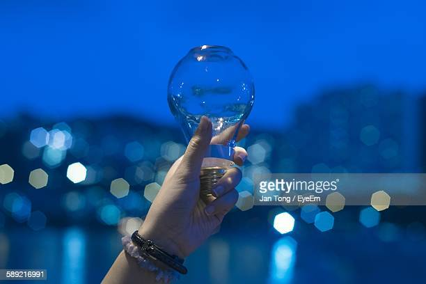 Cropped Hand Of Woman Holding Light Bulb With Water Against Sky