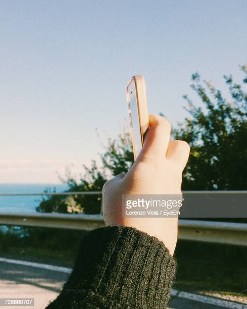 Cropped Hand Of Woman Holding Mobile Phone Against Sky