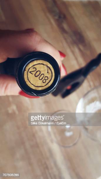 Cropped Hand Of Woman Holding Wine Bottle With Number On Cork