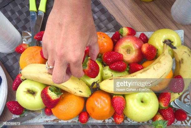 Cropped Hand Of Woman Picking Strawberry From Plate At Table