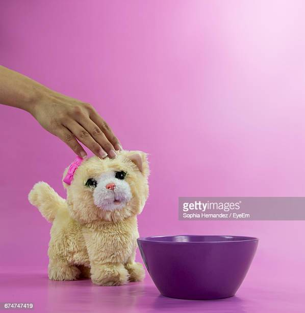 Cropped Hand Of Woman Touching Toy Cat By Bowl Against Pink Background