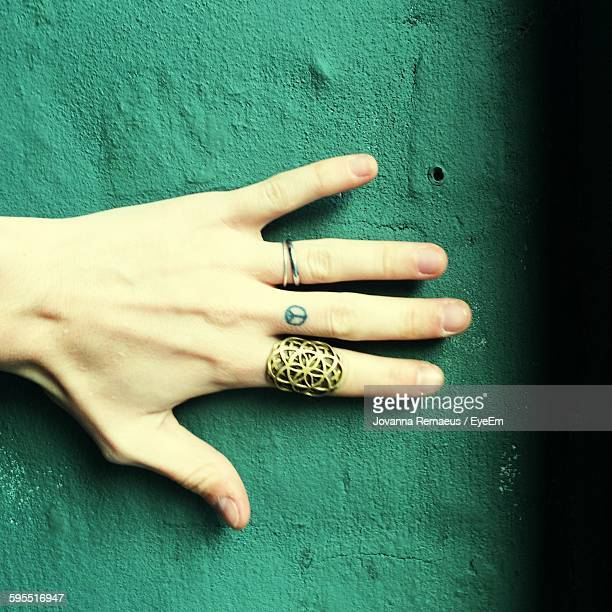Cropped Hand Of Woman Wearing Ring Against Green Wall