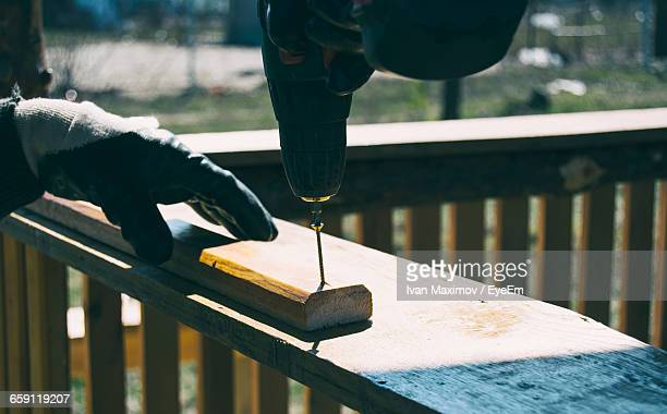 Cropped Hand Of Worker Drilling Screw On Wood