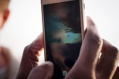 Cropped Hand Photographing Sunset In Mobile Phone