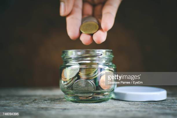 Cropped Hand Putting Coin In Glass Container On Wooden Table