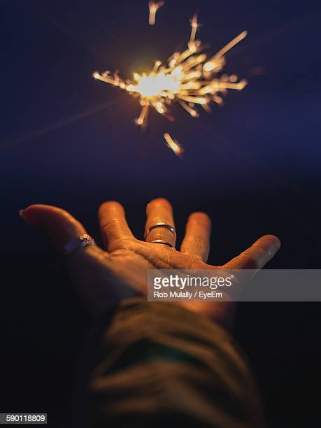 Cropped Hand Reaching Towards Sparkler At Night
