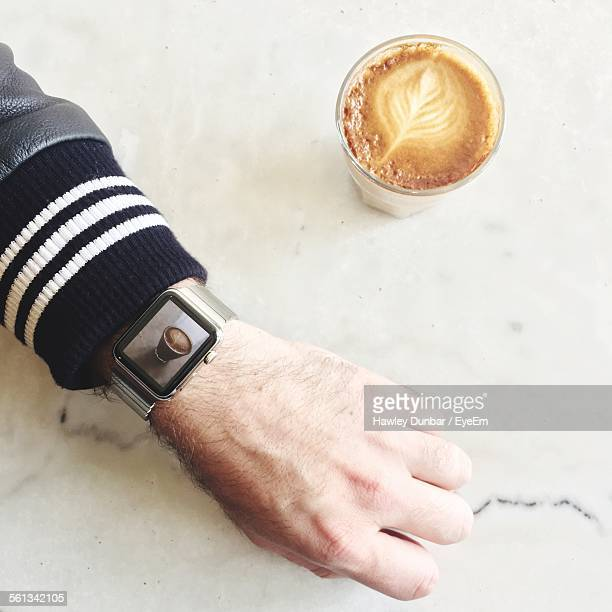 Cropped Hand Showing Coffee Cup In Smart Watch