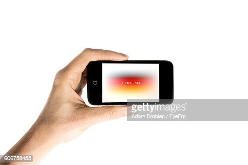 Cropped Hand Showing I Love You Text In Smart Phone Against White Background