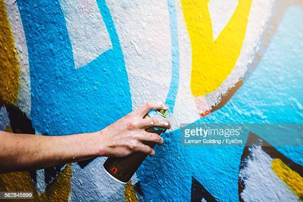 Cropped Hand Spraying Paint On Wall