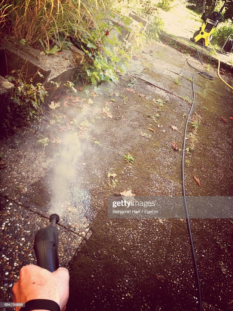 Cropped Hand Spraying Water On Walkway Using Pipe